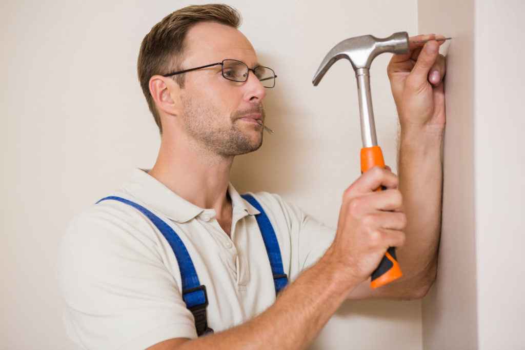 Delaware County Handyman Installing Nails To Hang Pictures And Other Things On The Wall